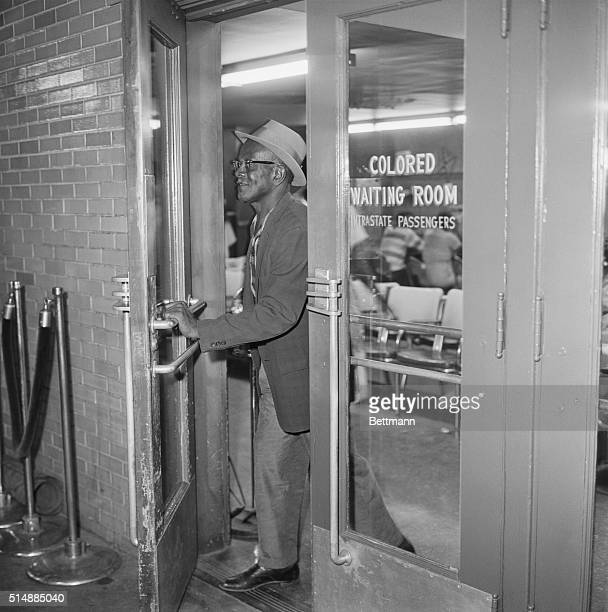 An African American passenger exits the 'Colored Waiting Room' at the Trailway Bus Terminal in Jackson, Mississippi.