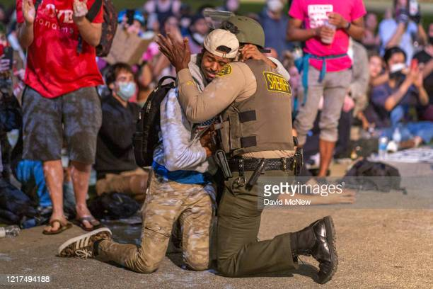 An African American protester and an African American Los Angeles County Sheriff's Department deputy embrace in solidarity as officers prepare to...