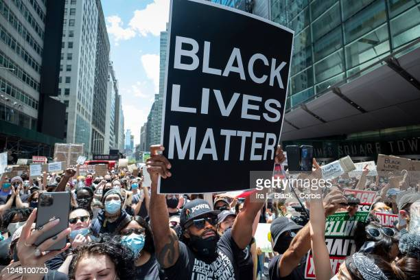 An African American protester wearing a mask around his neck and a hat that has Black Power in Times Square holds up a large sign that reads Black...