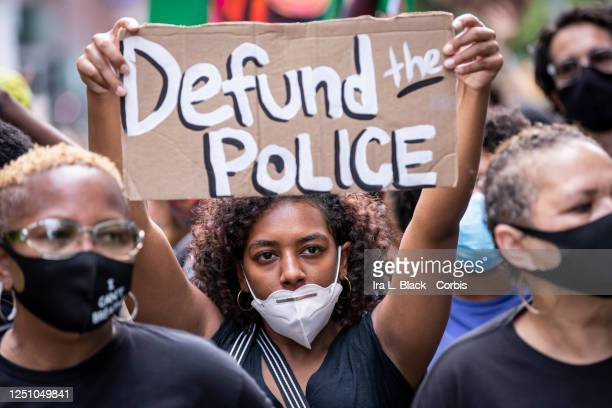 """An African American protester wears a mask and holds a homemade sign that says, """"Defund the Police"""" as they perform a peaceful protest walk across..."""