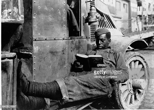 An African American soldier reads a book while resting on an ATS salvage truck shortly after World War I SaintNazaire France April 6 1919