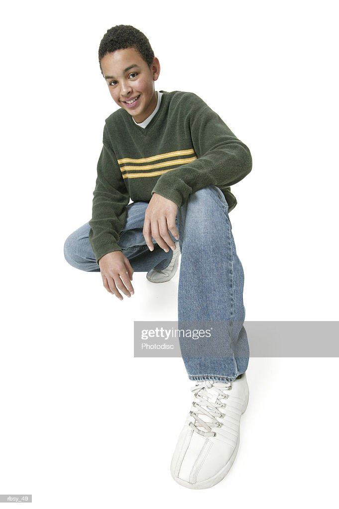 an african american teenage boy in jeans and a green sweater crouches down and smiles to the smiles : Foto de stock