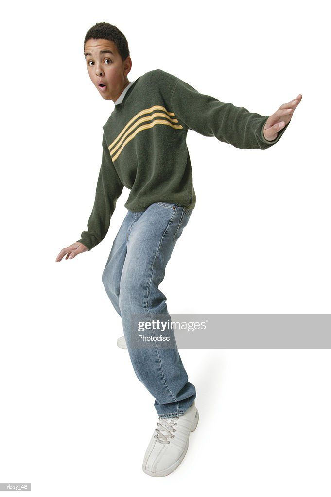 an african american teenage boy in jeans and a green sweater throws out his arms and strikes a fun surfing pose : Foto de stock