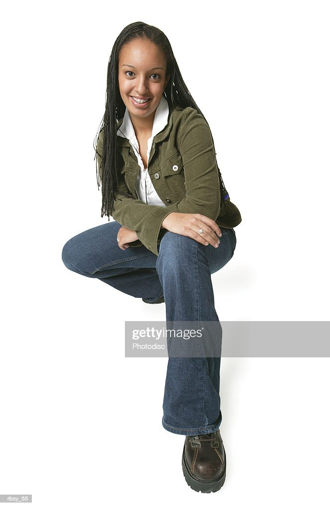 an african american teenage girl in jeans and a green jacket as she crouches down and smiles : Foto de stock