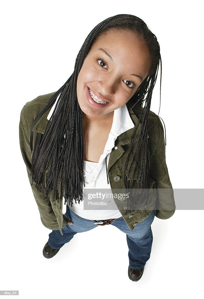 an african american teenage girl in jeans and a green jacket smiles up at the camera : Foto de stock