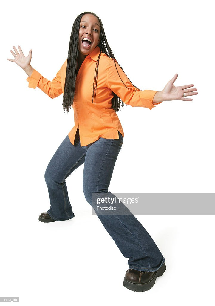 an african american teenage girl in jeans and an orange shirt spreads out her arms and smiles big : Foto de stock