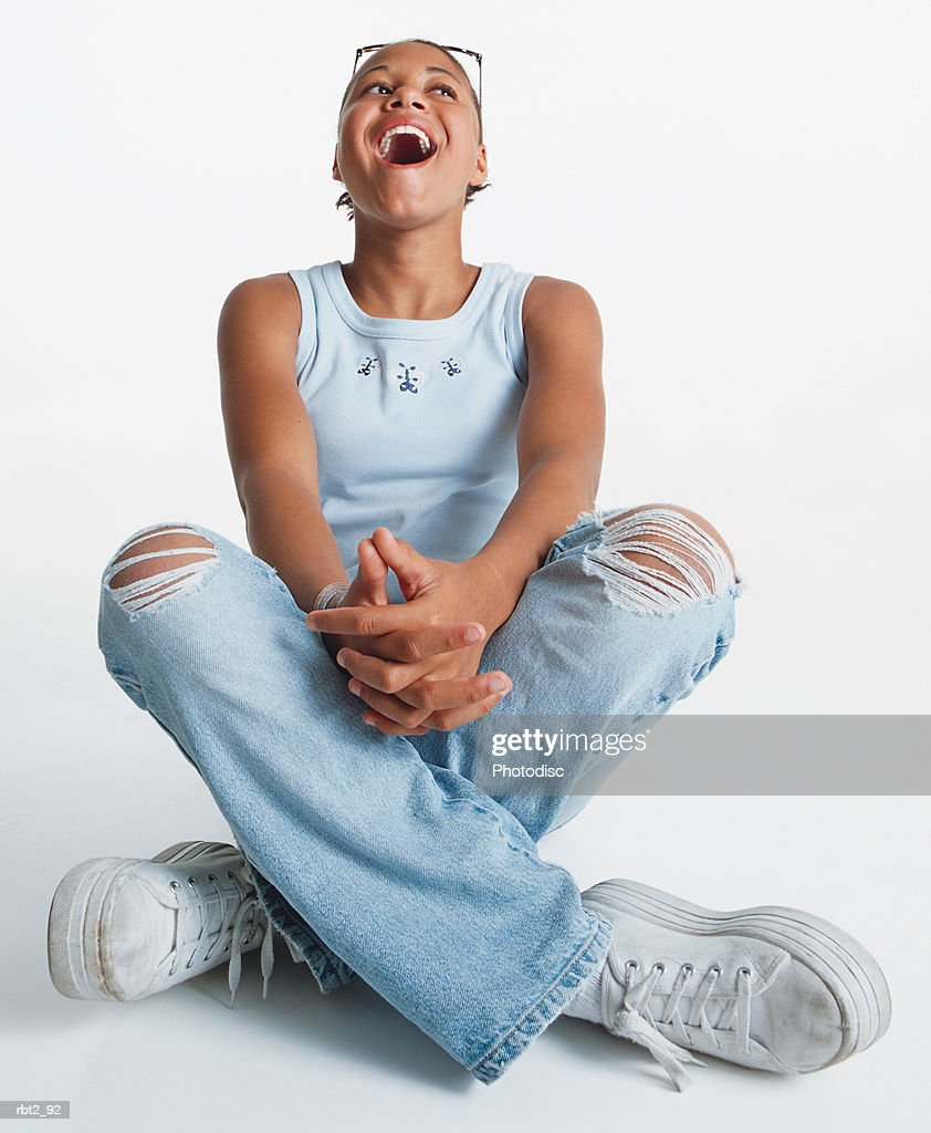 an african american teenage girl wearing jeans with holes in the kness sits crossleg on the floor as she throws her head back and laughs : Foto de stock