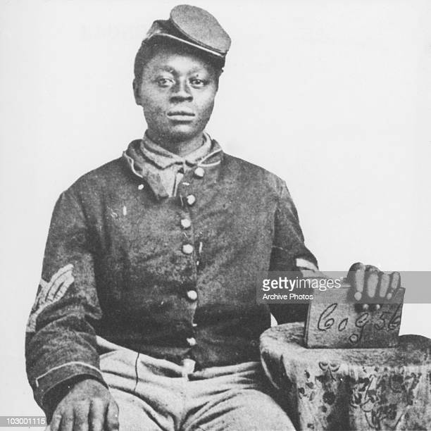 An African American Union soldier of the American Civil War seated in a studio portrait USA circa 1863 The soldier holds a book in his left hand with...