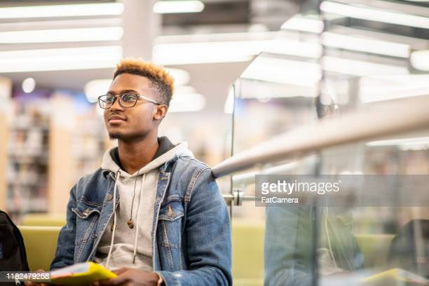 an african american university student studying in the library stock photo - 20 29 years stock pictures, royalty-free photos & images