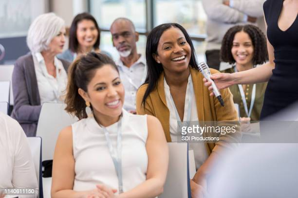 an african american woman asks a question - town hall stock pictures, royalty-free photos & images