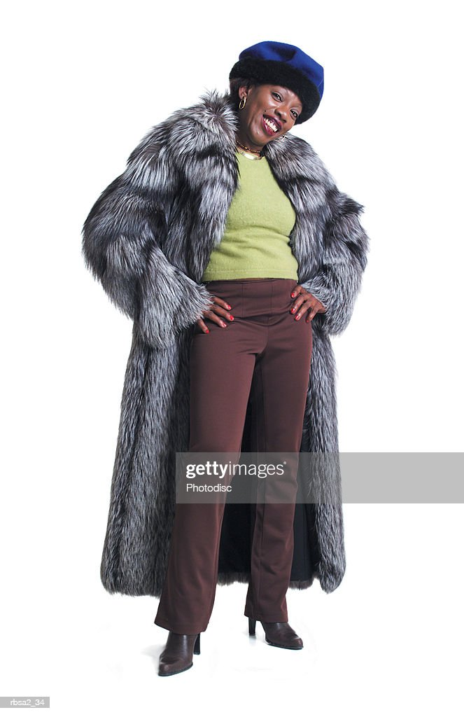 an african american woman in a dressed in a fur coat puts her hands on her hips smiles : Foto de stock
