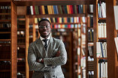 An African AmericanAn African American man in a business suit standing in a library in the reading room man in a business suit standing in a library in the reading room.