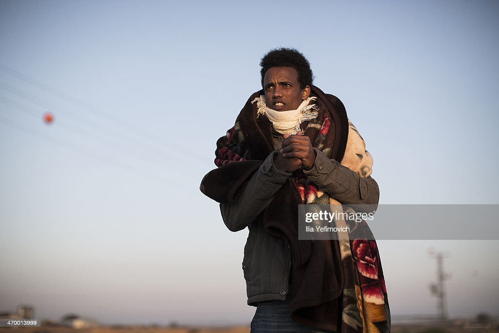 An African asylum seeker awakes ready for a second day of protest outside the Holot detention centre where hundreds of migrants are being held February 18, 2014 in the southern Negev desert of Israel. More than 50,000 illegal African migrants are seeking asylum after escaping war and government repression in their native lands.