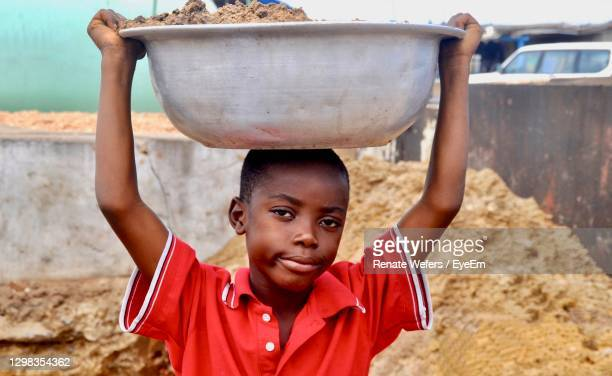 an african boy carries a bowl of sand on his head - 児童就労 ストックフォトと画像