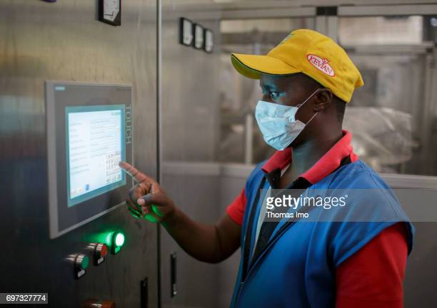 An African employee operates a technical system via touch display Production of pineapple juice at beverage manufacturer Kevian Kenya Ltd on May 18...
