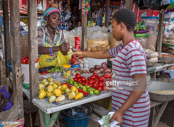 An African hawker sells a customer food at a market in Accra on September 08 2016 in Accra Ghana
