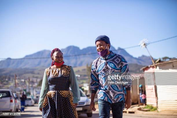 an african man and woman walking to work in kayamandi township. - township stock pictures, royalty-free photos & images