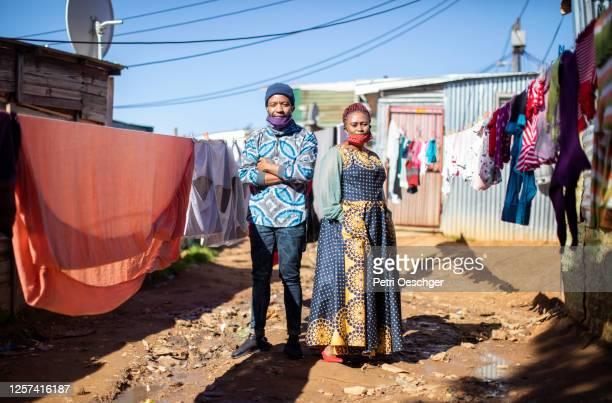an african man and woman walking to work in kayamandi township. - província do cabo ocidental imagens e fotografias de stock