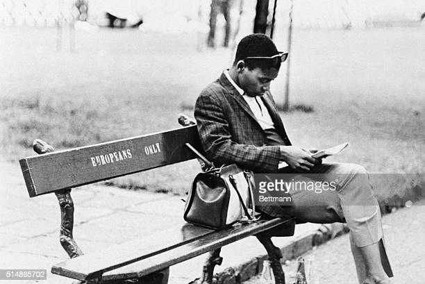 An African man reads on a bench marked 'Europeans Only' in a South African park