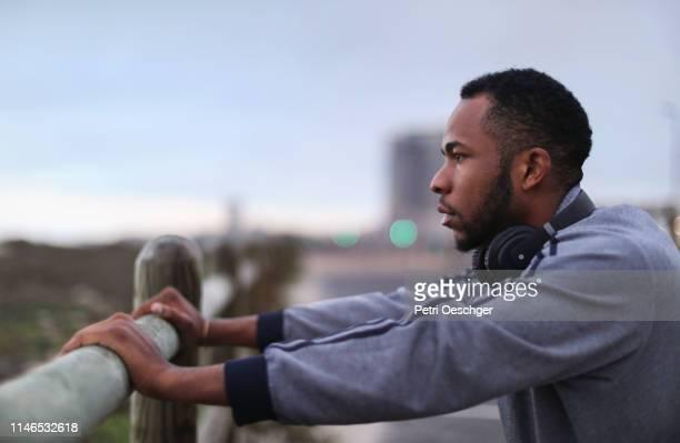 ein afrikanischer mann ruht gegen einen zaunpfahl. - bildschärfe stock-fotos und bilder