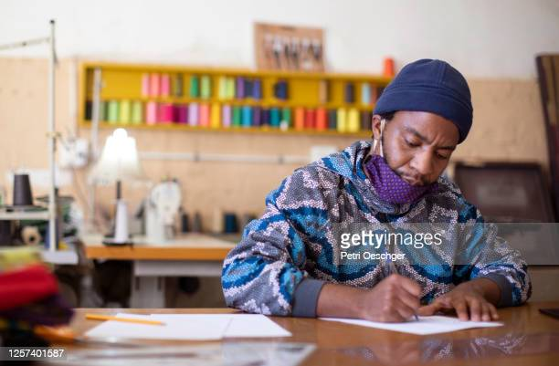 an african man sketching a design in his fashion design studio in kayamandi south africa. - black culture stock pictures, royalty-free photos & images