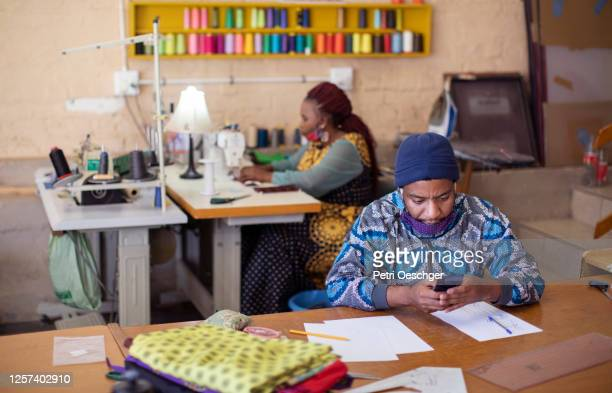 an african man using his mobile phone while sketching designs in his fashion studio. - township stock pictures, royalty-free photos & images