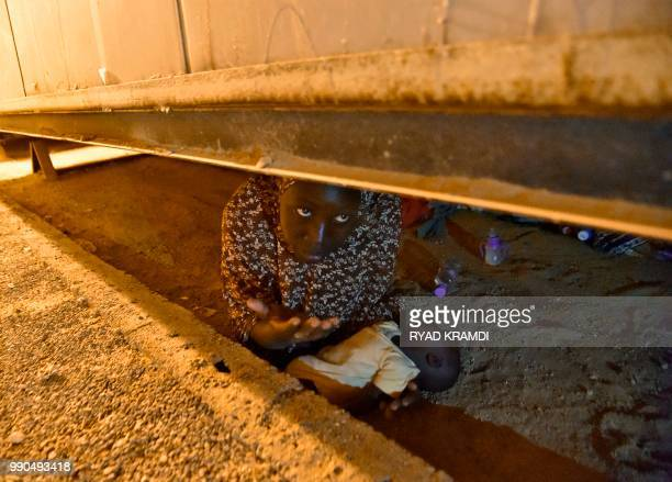 TOPSHOT An African migrant from Niger hides with her newborn child under a structure as she tries to avoid deportation on July 2 2018 at a transit...