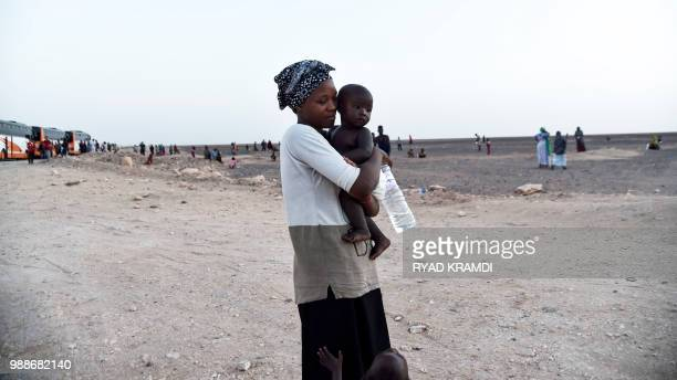 An African migrant from Niger stands with children during a temporary stop on the way to a transit centre for migrants about 200 kilometres north of...
