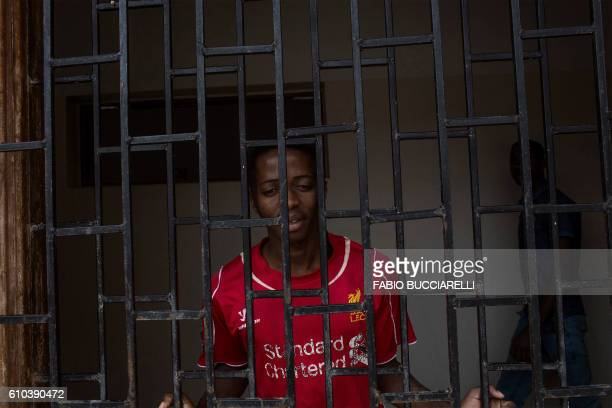 TOPSHOT An african migrant peers through a window at Libya's Karareem detention centre near Misrata a town halfway between Sirte and Tripoli on...