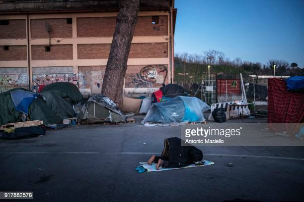An African migrant prays in the makeshift camp for migrants and refugees despite the low temperatures during the winter season on February 13 2018 in...
