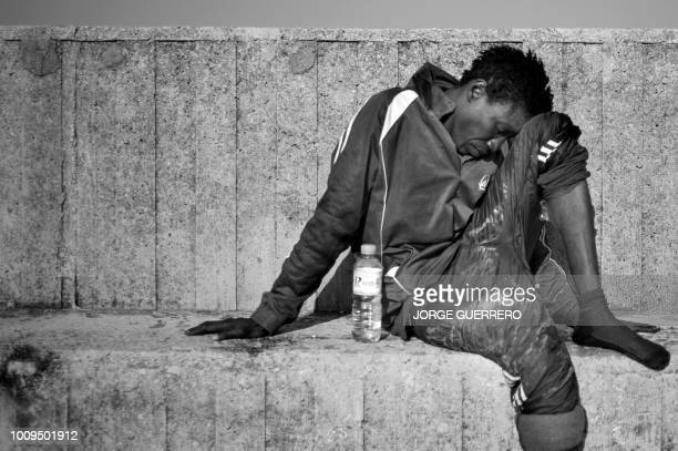 An African migrant rests at Algecira's harbour on July 14 after arriving onboard a Spanish coastguard boat following the rescue of and inflatable...