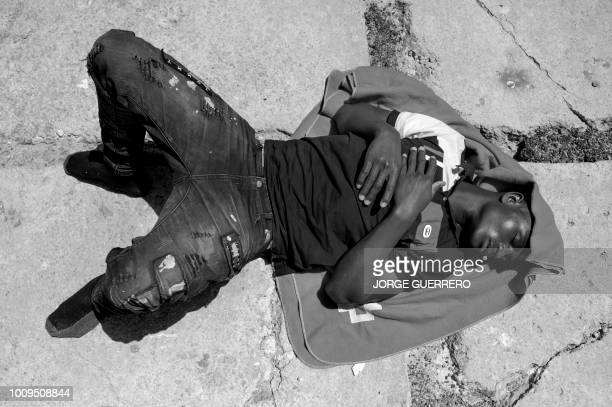 An African migrant sleeps at the harbour of Tarifa on July 24 after an inflatable boat carrying 135 people was rescued by the Spanish coast guard in...