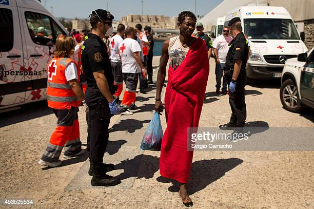 An African migrant walks after onshore after being rescued by a Spanish coast guard vessel in the port of Tarifa on August 12 2014 in Tarifa Spain...