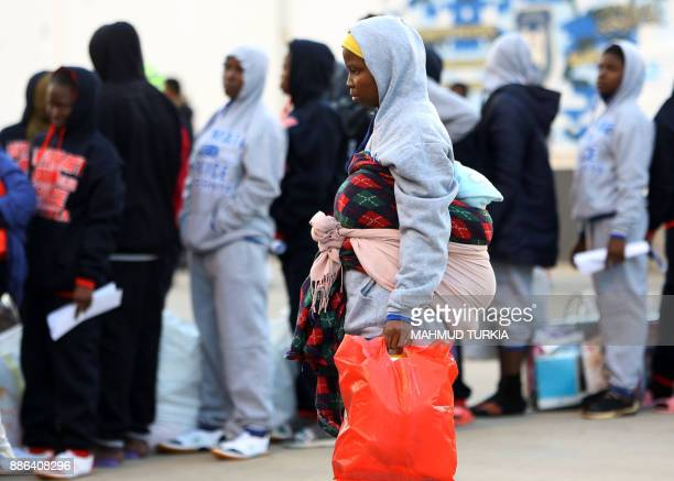 TOPSHOT An African migrant woman queues to receive clothing aid prior to repatriation at a detention center in the Libyan capital Tripoli's eastern...