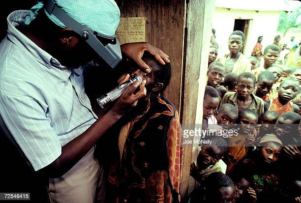 An African Ministry of Health worker with opthamology training Sidney Katala examines a child for signs of tracoma 1992 in Kongwa Tanzania Six out of...