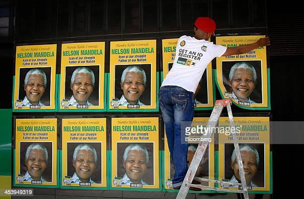 An African National Congress employee attaches posters to the outside of the political party's headquarters following the announcement of the death...