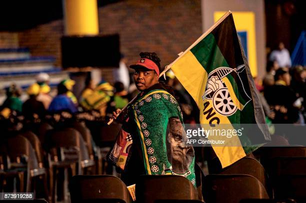 An African National Congress supporter walks with the party's flag as South African Deputy President and ruling party African National Congress...