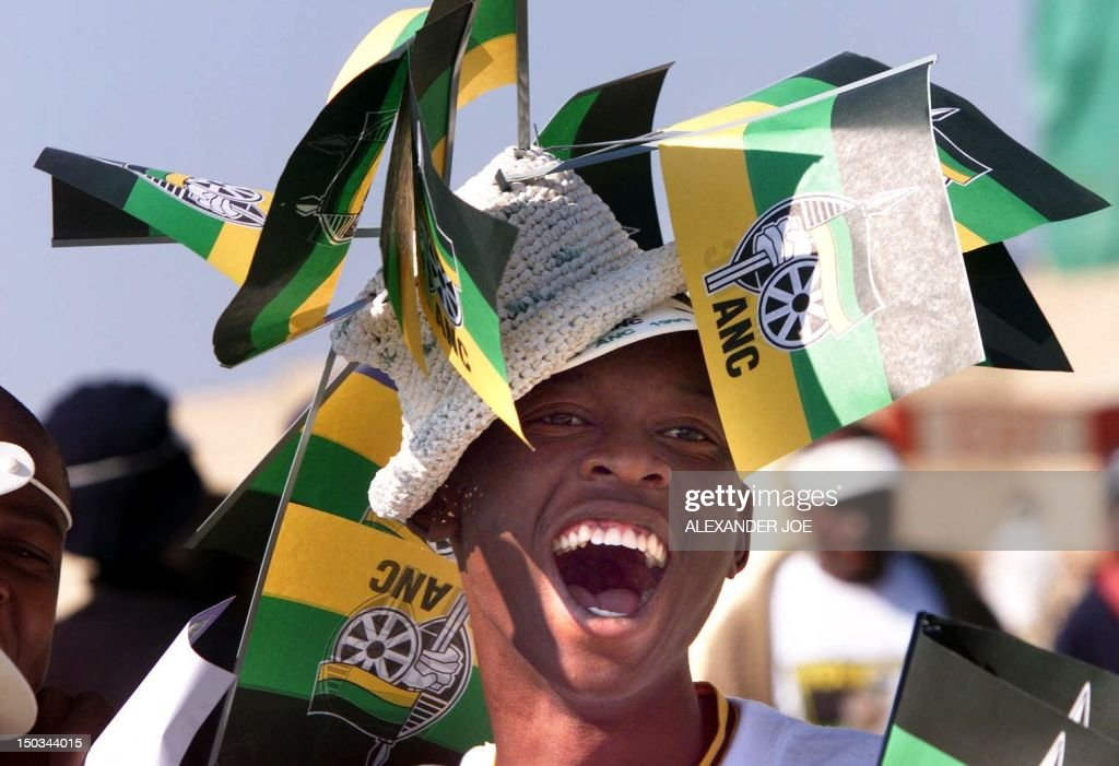 An African National Congress (ANC) supporters wearing flags shouts with the crowd to welcome South African President Nelson Mandela and deputy President Thabo Mbeki at the FNB stadium in Johannesburg 30 May 1999. A crowd of some 100,000 people came to bid Mandela farewell at his last rally before stepping down as president 16 June after the 02 June general elections. .(ELECTRONIC IMAGE) / AFP / ALEXANDER JOE