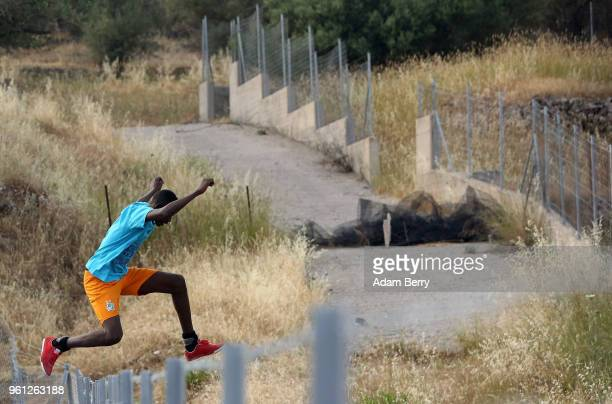 An African refugee jumps a fence to retrive a football after it went over the fence of a makeshift football pitch on a private locked parking lot...