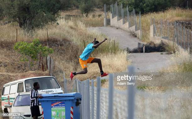 An African refugee jumps a fence while playing soccer to retrieve the ball after it went over the fence of a makeshift soccer field on a private...
