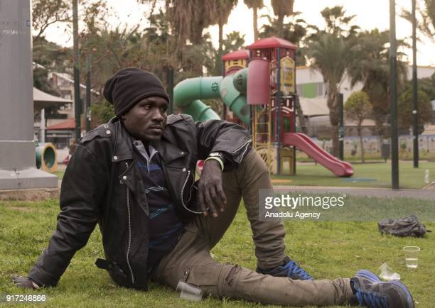 An African refugee man who lives in Israel is seen on the ground at a park in Tel Aviv Israel on February 10 2018 Israeli government offers an option...