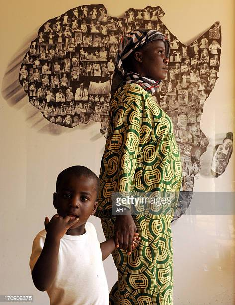 An African refugee walks with her son on June 17 2013 past a map of Africa at an exhibition hall in Rabat where refugees have been attending...