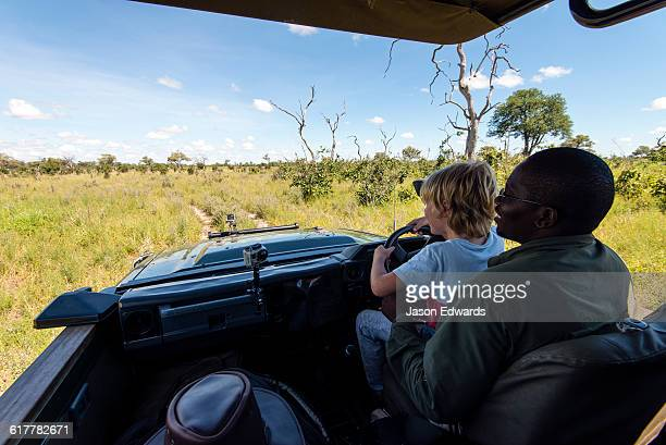 An African safari guide teaching a boy to drive a 4wd.