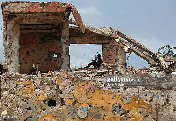 An African Union soldier looks out from war rubble on August 19, 2011 in Mogadishu, Somalia. After two decades of civil war in Mogadishu, the capital...
