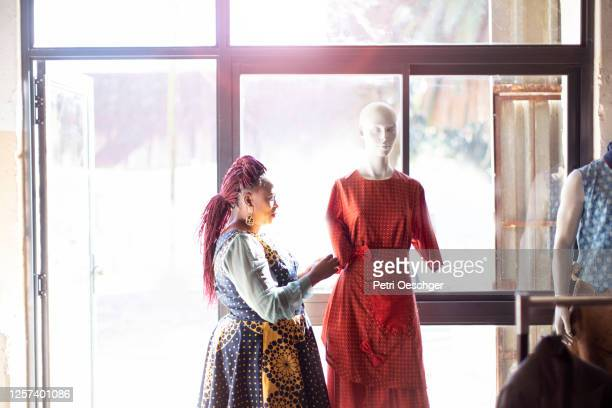 an african woman adjusting clothing on a mannequin in her studio. - township stock pictures, royalty-free photos & images