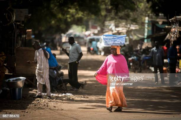 An African woman carries a laundry basket on her head Street scene in Bamako on April 07 2017 in Bamako Mali