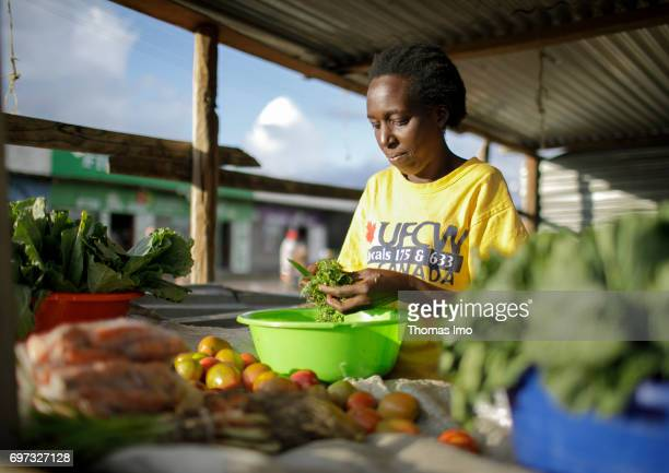 An African woman cuts herbs at a market on May 17 2017 in Talek Kenya