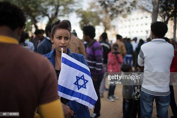 An African woman holds an Israeli flag as thousands of African migrants take part in a rally on January 7 2014 in Tel Aviv Israel Tens of thousands...
