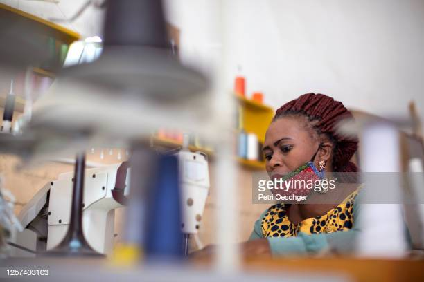 an african woman making face masks in her fashion design studio. - township stock pictures, royalty-free photos & images