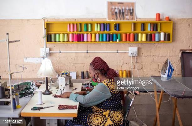een afrikaanse vrouw die gezichtsmaskers in haar studio van het manierontwerp maakt. - gemeente stockfoto's en -beelden